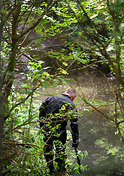 © Licensed to London News Pictures. 24/07/2013 London, UK. A member of the Underwater and Confined Space Search Unit walks along a stream investigating the murder of a young Hungarian national who's body was found in a suitcase on Sunday (July 21st). A 29 year old has been arrested on suspicion of murdering the young woman found dead in Thornfield Avenue, North West London.<br /> Photo credit : Simon Jacobs/LNP