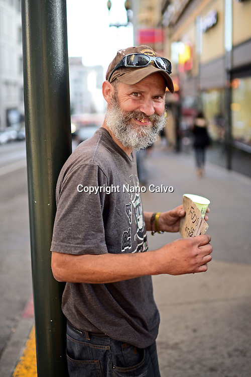 "Perrie, kind homeless man from Michigan, poses in the streets of San Francisco with a sign that reads ""Smile"", California."