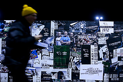A Derby County fan walks past a poster of Wayne Rooney of Derby County outside Pride Park Stadium - Mandatory by-line: Robbie Stephenson/JMP - 02/01/2020 - FOOTBALL - Pride Park Stadium - Derby, England - Derby County v Barnsley - Sky Bet Championship