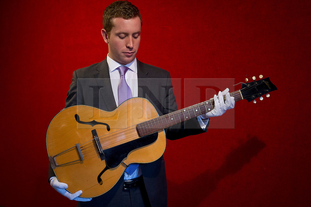 © Licensed to London News Pictures. 10/12/2012. London, UK. A member of Bonham's staff holds a guitar used by Paul McCartney (est. GB£20,000-30,000) when he was part of the pre-Beatles band 'the Quarry Men' at an auction press view in Knightsbridge, London, today (10/12/12). . The entertainment memorabilia auction, set to take place at Bonham's Knightsbridge auction house on the 12th of December, features props and costumes from film and TV as well as important Beatles pieces. Photo credit: Matt Cetti-Roberts/LNP