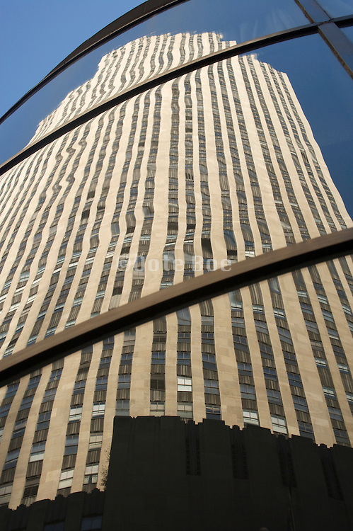 Rockefeller Center building reflecting in a glass high rise from across the street