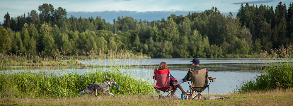 A couple relaxes on a warm evening at Anchorage's Westchester Lagoon.