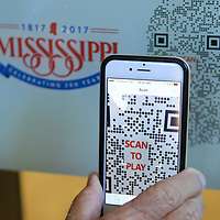 Danny McKenzie, of Tupelo, scans a photo at the Renasant Bank location to view a video on a Tupelo Bicentennial Photo Project photograph on Thursday morning.