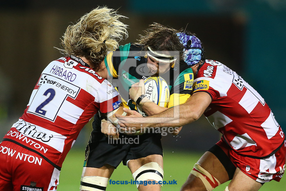 Tom Wood of Northampton Saints (centre) is tackled by Richard Hibbard of Gloucester Rugby (left) and Mariano Galarza of Gloucester Rugby (right) during the Aviva Premiership match at Franklin's Gardens, Northampton<br /> Picture by Andy Kearns/Focus Images Ltd 0781 864 4264<br /> 28/10/2016