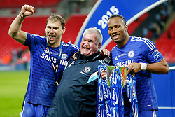 Branislav Ivanovic and Didier Drogba of Chelsea pose with Player Liason Officer Gary Staker and the League Cup Trophy after winning the Capital One Cup Final - Photo mandatory by-line: Rogan Thomson/JMP - 07966 386802 - 01/03/2015 - SPORT - FOOTBALL - London, England - Wembley Stadium - Chelsea v Tottenham Hotspur - Capital One Cup Final.