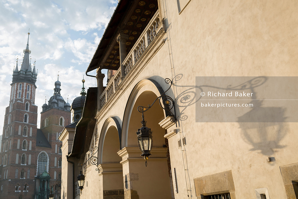 Morning light on Renaissance architecture of the Church of St Mary (left) and the Renaissance Cloth Hall on Rynek Glowny market square, on 23rd September 2019, in Krakow, Malopolska, Poland.