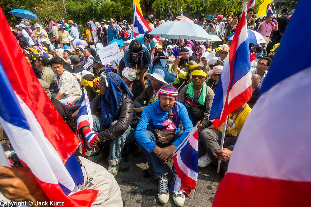 """09 DECEMBER 2013 - BANGKOK, THAILAND:  Anti-government protestors block the road that leads to Government House in Bangkok. Thai Prime Minister Yingluck Shinawatra announced she would dissolve the lower house of the Parliament and call new elections in the face of ongoing anti-government protests in Bangkok. Hundreds of thousands of people flocked to Government House, the office of the Prime Minister, Monday to celebrate the collapse of the government after Yingluck made her announcement. Former Deputy Prime Minister Suthep Thaugsuban, the organizer of the protests, said the protests would continue until the """"Thaksin influence is uprooted from Thailand."""" There were no reports of violence in the protests Monday.     PHOTO BY JACK KURTZ"""