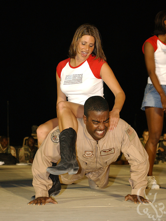 A cheerleaders for the American football team the Baltimore Ravens sits atop U.S. Air Force SRA Alvin Haymond as he competes in a push-up competition at the coalition forces'' Kandahar airfield May 08, 2002 in southern Afghanistan. The cheerleaders are visiting the airbase as part of a USO Tour for coalition forces deployed across the Middle East and Central Asia for Operation Enduring Freedom..
