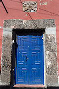 A colonial style blue wooden door along Loreto Street in the colonial UNESCO heritage city of San Miguel de Allende, Mexico.