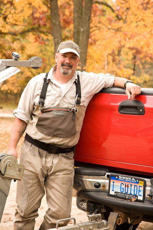A Fly fishing guide relaxes at his truck after a float down Michigan's Pere Marquette River.