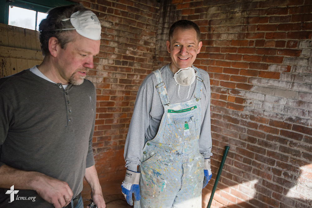 "The Rev. Thomas Eggold (right) talks to architect Scott Greider as the two assist volunteers and members of Emmanuel Lutheran Church as they rehab a vacant and abandoned home adjacent to the church on Saturday, April 12, 2014, in Ft. Wayne, Ind.  The rehab is part of the ""Helping Hand""  initiative from the LCMS National Housing Support Corporation (NHSC) and a coalition of church partners, including Redeemer Lutheran, Emmanuel Lutheran, Zion Lutheran, and St. Peter's Catholic. The initiative is a multi-neighborhood safe housing and repair effort that plans to support nine low-income and/or elderly homeowners. LCMS Communications/Erik M. Lunsford"