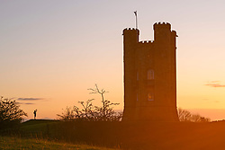 © Licensed to London News Pictures. 07/11/2019. Broadway, Worcestershire, UK. A man takes a photograph as the sun sets over the Cotswolds behind Broadway Tower on a cold autumnal evening in Worcestershire. Photo credit: LNP