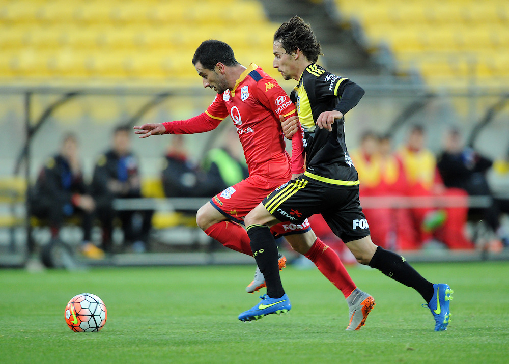 Adelaide United's Sergio Cirio, left and Phoenix's Albert Riera chase down the ball in the A-League football match at Westpac Stadium, Wellington, New Zealand, Friday, November 13, 2015. Credit:SNPA / Ross Setford