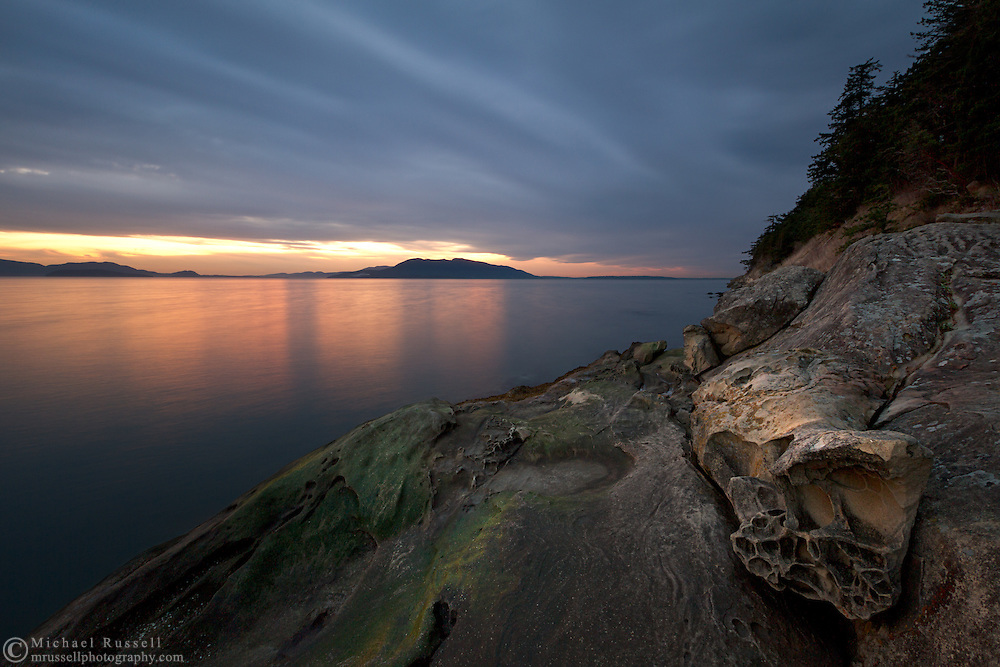 Sunset over Lummi Island and sandstone Tafoni at Clayton Beach in Larrabee State Park - Bellingham, Washington State, USA