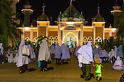 11 JULY 2013 - PATTANI, PATTANI, THAILAND:   Women walk into the Pattani Central Mosque in Pattani, Thailand, Thursday night for Ramadan services. The mosque is one of the busiest in south Thailand. About 15,000 people attend nightly Ramadan services in the mosque. Ramadan is the ninth month of the Islamic calendar, and the month in which Muslims believe the Quran was revealed. Muslims believe that the Quran was sent down during this month, thus being prepared for gradual revelation by Jibraeel (Gabriel) to the Prophet Muhammad. The month is spent by Muslims fasting during the daylight hours from dawn to sunset. Fasting during the month of Ramadan is one of the Five Pillars of Islam.    PHOTO BY JACK KURTZ