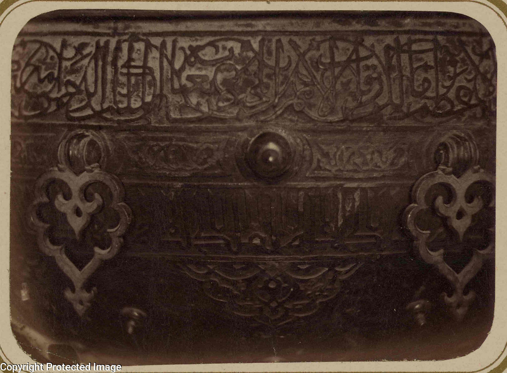 1865<br /> This photograph of a detail of a ritual basin in the interior of the mausoleum of Khodzha Akhmed Iassavi in Yasi (present-day Turkestan, Kazakhstan) is from the archeological part of Turkestan Album. The six-volume photographic survey was produced in 1871-72 under the patronage of General Konstantin P. von Kaufman, the first governor-general (1867-82) of Turkestan, as the Russian Empire&rsquo;s Central Asian territories were called. Yasi is associated with the Sufi mystic, Khodzha Akhmed Iassavi (1103-66), whose great reputation led Timur (Tamerlane) to construct a memorial shrine (khanaka) at his grave site. Built in 1396-98, the mausoleum displays features of Timurid architecture, then at its height in Samarkand. This view shows part of a large bronze ritual water basin, stated by an inscription on the basin to have been donated by Timur. The basin is elaborately decorated with botanical figures and Perso-Arabic inscriptions. At the top is a band of Naskh script intertwined with a tendril pattern. Below this band are decorative bronze fittings and another inscription, in block letters. On the curved surface at the bottom of the photograph is an arabesque figure. The height of the basin is about one meter.