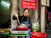 "23 DECEMBER 2017 - HANOI, VIETNAM: A woman cooks street food in the old quarter of Hanoi. The old quarter is the heart of Hanoi, with narrow streets and lots of small shops but it's being ""gentrified"" because of tourism and some of the shops are being turned into hotels and cafes for tourists and wealthy Vietnamese.      PHOTO BY JACK KURTZ"