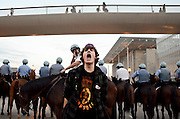"An Occupy Chicago protester confronts mounted police on East Monroe Street outside of the Art Institute of Chicago on October 10, 2011 during a cocktail reception on the museum rooftop for members of the U.S. futures industry trade group. Protester chants targeted the so called ""one percent"" during the traders' event over growing restlessness on economic inequality and joblessness."