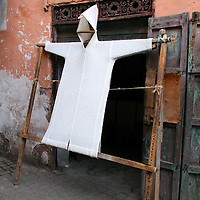 North Africa, Africa, Morocco, Marrakesh. A traditional Morrocan robe, or djellaba, stretched and drying outside shop of Marrakesh.