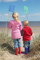 Brother and sister (4-6) with fishing nets standing on sand dunes