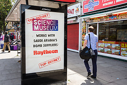 London, UK. 12 July, 2019. A poster at a bus shelter in Finsbury Park by street art collective Protest Stencil draws attention to the Science Museum having partnered with Raytheon, a US weapons manufacturer which sells arms used by Saudi Arabia for attacks on civilian areas in Yemen, for sponsorship of its new 'Top Secret' exhibition. Protest Stencil last week withdrew artwork from the exhibition in protest against Raytheon's sponsorship.
