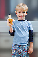 Portrait of Caucasian boy in casuals holding banana
