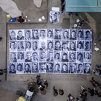 Geneva, Switzerland 15th March 2016. Aerial photo of a portraits of asylum seekers in Geneva being pasted on to the ground at a busy intersection in the Plainpalais  district, by the asylum seekers themselves. The portraits are of people from diverse countries including Syria, Eritrea  Afghanistan Iraq, Nigeria, Guinea, Sri Lanka and Somalia, many of them housed in bunkers, and are among the around 7000 asylum seekers in this Canton of population of just under half a million, housed by the Hospice General. The photos, by British photographer Mark Henley are part of an Inside Out project,from the foundation set up by French artist JR. An action during the Anti-racism Week Photo Credit: Sebastian Moret.