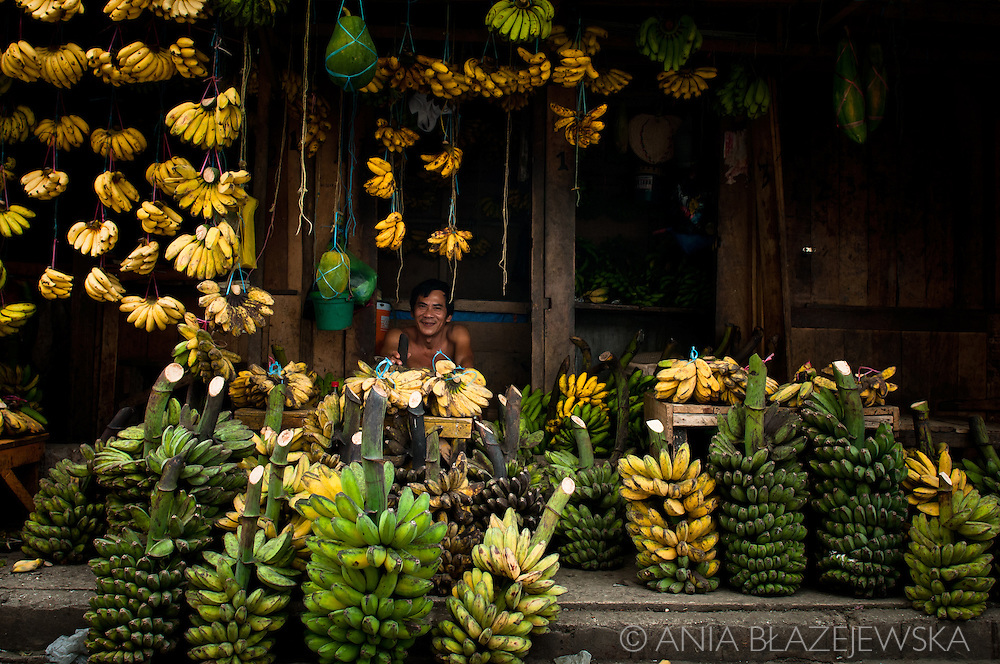 Philippines, Tawi Tawi. Banana seller running a small stand in the market in Bongao.