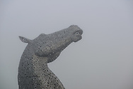 The Kelpies appear out of the freezing fog. The Kelpies 30-metre high horse-head sculptures, standing next to the Forth and Clyde Canal, in The Helix, a parkland project in the Falkirk Council Area, Scotland. Designed by sculptor Andy Scott and bult from stainless steel, The Kelpies are mystical water-borne equine creatures which celebrate the horse's role in industry and agriculture.