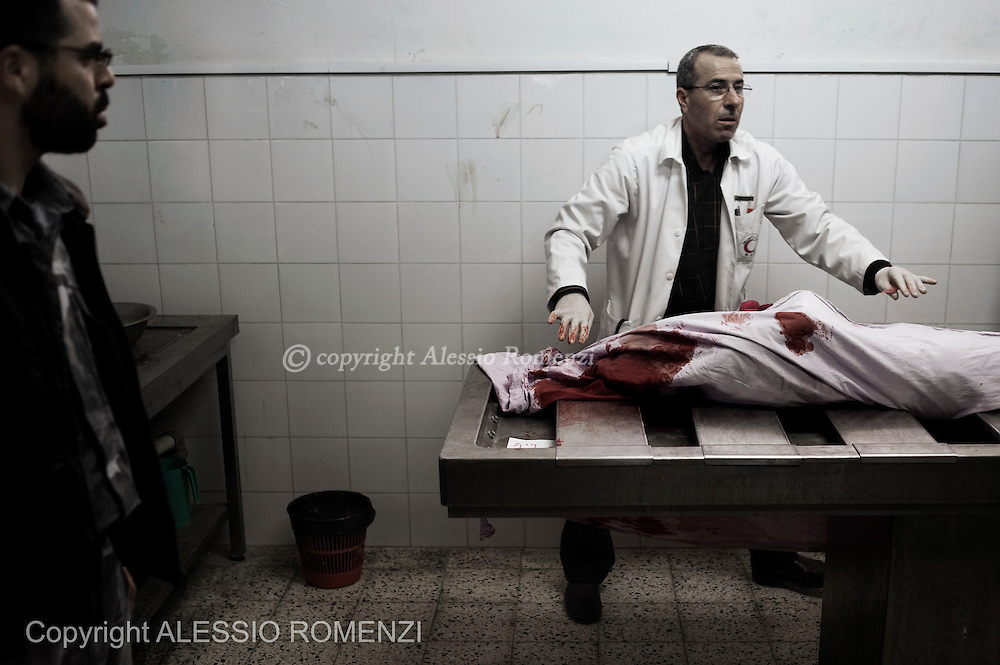 Gaza City: Tasneem al-Nahal, 13, is wrapped in a bloody blanket in the morgue of the al-Shifa hospital in Gaza City after she was killed by an Israeli airstrike in Shati refugee camp. November 18, 2012. ALESSIO ROMENZI