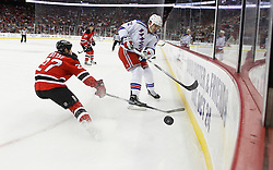 Oct 5, 2009; Newark, NJ, USA; New York Rangers center Brian Boyle (22) flips the puck past New Jersey Devils defenseman Mike Mottau (27) during the first period at the Prudential Center.
