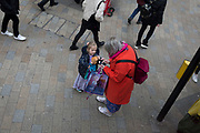 A young girl stands next to an older lady who is using her mobile phone in the street, on 31st January 2020, in London, England.