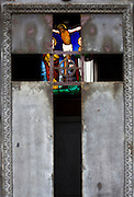 Montparnasse Cemetery, Paris. Stained glass window of the crucifixion seen through the door of tomb.