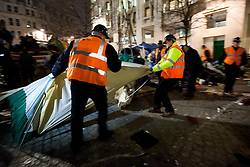 © Licensed to London News Pictures. 28/02/2012. LONDON, UK. Workers remove tents as bailiffs and police evict Occupy London protesters from their campsite. After being camped outside St Paul's Cathedral in London for four months anti-capitalist Occupy London demonstrators were tonight evicted by police and bailiffs who moved in shortly after midnight. Photo credit: Matt Cetti-Roberts/LNP