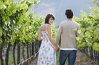 Rear view of young couple walking through vineyard hand in hand woman smiling back over her shoulder