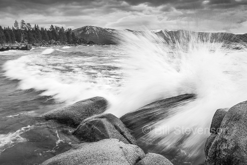 A black and white image of a wave splashing against a rock at Lake Tahoe in California.