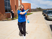 22 APRIL 2020 - DES MOINES, IOWA: A school staff person waves to students during computer distribution at Edmunds Elementary School. Schools in Iowa are closed for the rest of the school year because of the COVID-19 (Coronavirus/SAR-CoV-2) pandemic. Des Moines Public Schools expanded their school lunch and distance learning efforts this week. Lunches are being distributed at all of the district's elementary and middle schools and officials have started distributing computers so students can participate in distance learning.           PHOTO BY JACK KURTZ