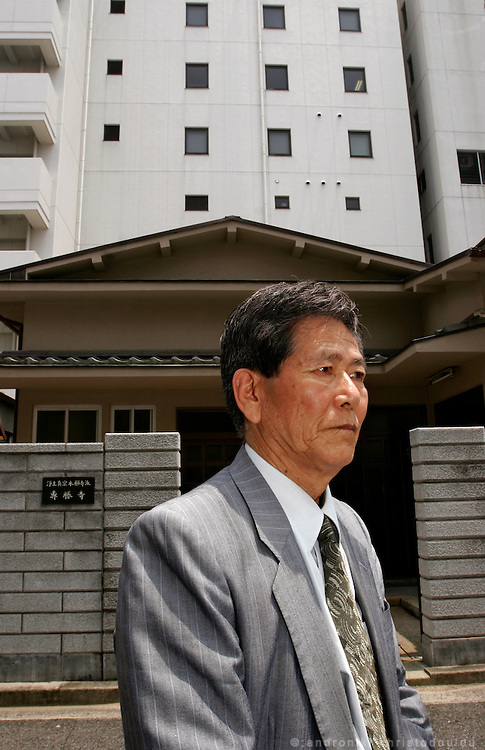 SEIJI TANI.  Hiroshima A-Bomb survivor. Student of IDEC, Hiroshima University. Standing in front of where his house used to be before the bombing. He found it because he remebered it was behing a temple. Now a chement building is at it's place and a new temple in place of the old one.