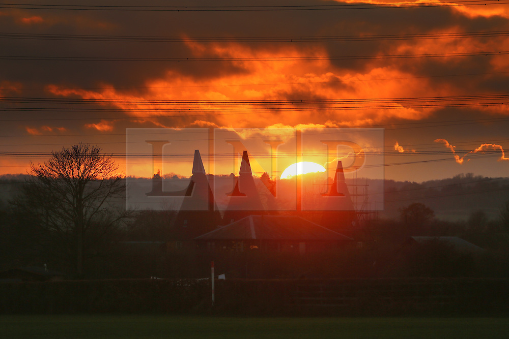 © Licensed to London News Pictures. 09/12/2013. The sunsetting over some oasthouses in Ifield, Kent, at the end of an unseasonally mild day. Credit : Rob Powell/LNP