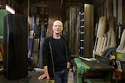Furniture maker Adrian Swintead describing work on 2 pieces (wooden cabinets in foreground and background) displayed in his Maulden Woods studio, Bedfordshire<br /> CREDIT: Vanessa Berberian for The Wall Street Journal<br /> GURU-SWINSTEAD