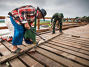 16 SEPTEMBER 2014 - SANGKHLA BURI, KANCHANABURI, THAILAND: A member of the Mon community and a Thai soldier pull old nails out of a piece of recycled lumber on the Mon Bridge. The 2800 foot long (850 meters) Saphan Mon (Mon Bridge) spans the Song Kalia River. It is reportedly second longest wooden bridge in the world. The bridge was severely damaged during heavy rainfall in July 2013 when its 230 foot middle section  (70 meters) collapsed during flooding. Officially known as Uttamanusorn Bridge, the bridge has been used by people in Sangkhla Buri (also known as Sangkhlaburi) for 20 years. The bridge was was conceived by Luang Pho Uttama, the late abbot of of Wat Wang Wiwekaram, and was built by hand by Mon refugees from Myanmar (then Burma). The wooden bridge is one of the leading tourist attractions in Kanchanaburi province. The loss of the bridge has hurt the economy of the Mon community opposite Sangkhla Buri. The repair has taken far longer than expected. Thai Prime Minister General Prayuth Chan-ocha ordered an engineer unit of the Royal Thai Army to help the local Mon population repair the bridge. Local people said they hope the bridge is repaired by the end November, which is when the tourist season starts.    PHOTO BY JACK KURTZ