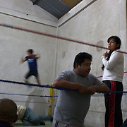 Yolanda La Amorosa (right)  training during a late evening training session with other members of the 'Titans of the Ring' at a makeshift gymnasium in El Alto, Bolivia . The wrestling group performs every Sunday at El Alto's Multifunctional Centre. Bolivia. The group includes the fighting Cholitas, a group of Indigenous Female Lucha Libra wrestlers who fight the men as well as each other for just a few dollars appearance money. El Alto, Bolivia, 28th January 2010. Photo Tim Clayton
