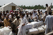 Residents from SWAT valley begin arriving at Shaik Shazad IDP camp at outside of Mardan in North West Frontier Province...Men and women queue for food handouts and blankets at a distribution point on the Shaik Shazad IDP Camp. riots later broke out at the camp where there not enough relief supplies for the amount of IDPs that had arrived during this day...Within four days more than 2000 families have reportedly registered as IDP's seeking shelter and food at the hastily arranged camp. According to UNHCR Some 500,000 residents have fled SWAT and neighboring provinces since August 2008. On Thursday the Pakistan Government announced a military operation to 'eliminate' Taliban militants form the SWAT Valley. A further 1 million IDP's are expected in the coming weeks as the military advances throughout SWAT valley towards achieving their military goals..