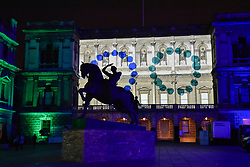 "© Licensed to London News Pictures. 17/01/2018. LONDON, UK.  The new equestrian statue ""Physical Energy"" by George Frederic Watts RA is seen in silhouette against ""Love Motion"" by Rhys Coren, a projection onto the Royal Academy in Piccadilly. Preview of Lumiere London, the capital's largest arts festival commissioned by The Mayor of London and produced by Artichoke.  Light installations by leading artists have been set up, both north and south of the river for the public to view 18-21 January.   Photo credit: Stephen Chung/LNP"