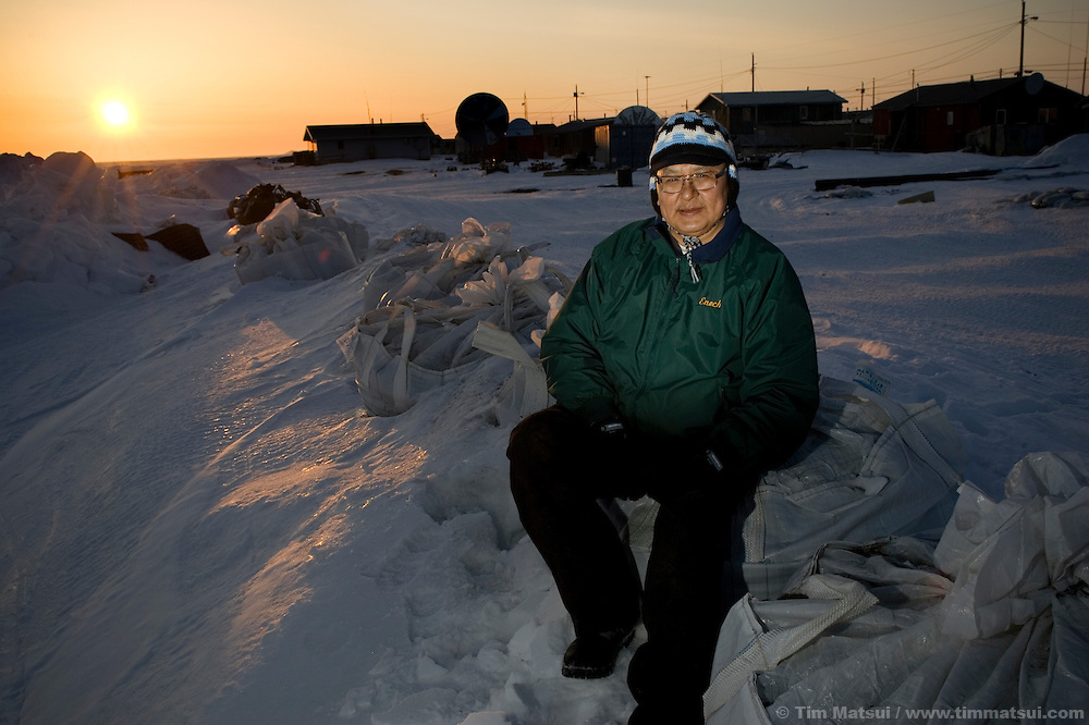 May 2, 2008 -- Kivalina, AK, U.S.A..Enoch Adams, a city official, reverend, and chief figure in the lawsuit initiated by the 400 person native village of Kivalina, Alaska, stands atop large sandbags buried in snow which demarcate the eroding seaward beach only feet from homes and permanent facilities. Kivalina is suing 20 oil companies for property damage related to global warming; the ocean pack ice forms later and melts earlier, leaving the town vulnerable to erosive winter storms and endangering their traditional subsistence lifestyle. (Photo by Tim Matsui)