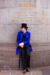LONDON, UK  29/04/2011. The Royal Wedding of HRH Prince William to Kate Middleton. A spectator in fancy dress takes a break under a statue of Boadicea on Westminster Bridge. Photo credit should read CLIFF HIDE/LNP.