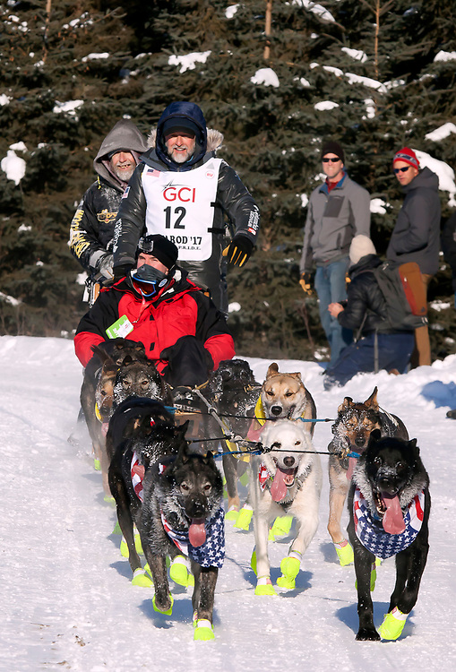 Alaska. Musher Joe Carson and team running through trails of Anchorage during the 2017 Iditarod Ceremonial start, Anchorage.