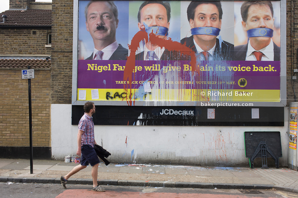 A voter walks past splashed paint over the anti-EU membership 'UK Independence Party's (UKIP) political billboard that shows leader Nigel Farage (with daubed Hitler moustache) and a gagged Prime Minister David Cameron, Labour party leader Ed Milliband and (coaltion) Deputy PM Nick Clegg - all silent against a bullying European Union, seen in East Dulwich - a relatively affluent district of south London. The ad is displayed before European elections on 22nd May.