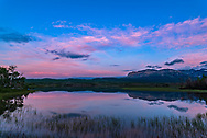 Two photographers and participants at my June 17, 2018 Night Photography Workshop in Waterton Lakes National Park, at Maskinonge, in the evening twilight, with the twilight colours over the lake. Two swans are in the distance. This was a magical evening. <br /> <br /> A single exposure with the Sigma 20mm lens and Nikon D750.