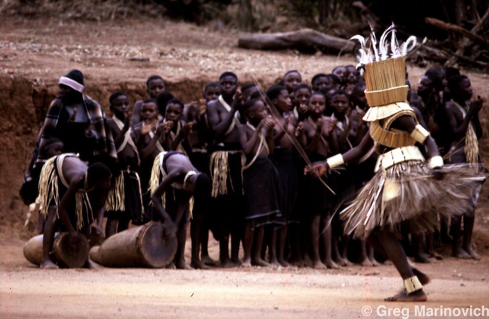 Vhawhera initiate masked in grass and reed dances before female intiates in the stockaded capital of the Lobedu people, ha-Modjadji, South Africa. (Greg Marinovich) horizontal colour slide.